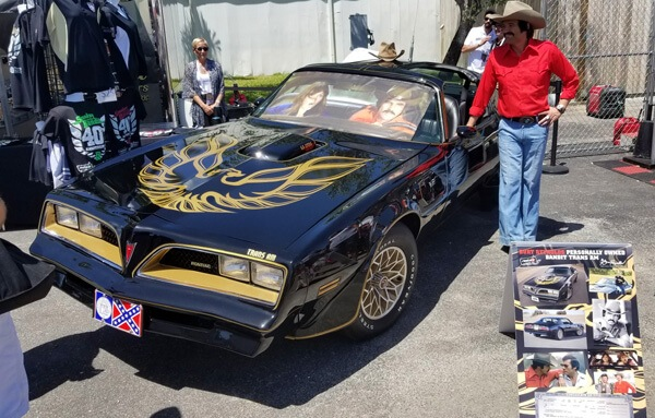 Burt Reynolds look-alike actor poses with fans next to the Bandit Trans Am