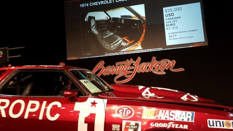 Video screen beside Barrett-Jackson Palm Beach auction block shows final bid on Burt Reynolds' Cannonball Run car at $35,000